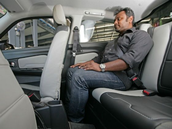 Muntaser demonstrates the legroom of the Mahindra e2o electric car